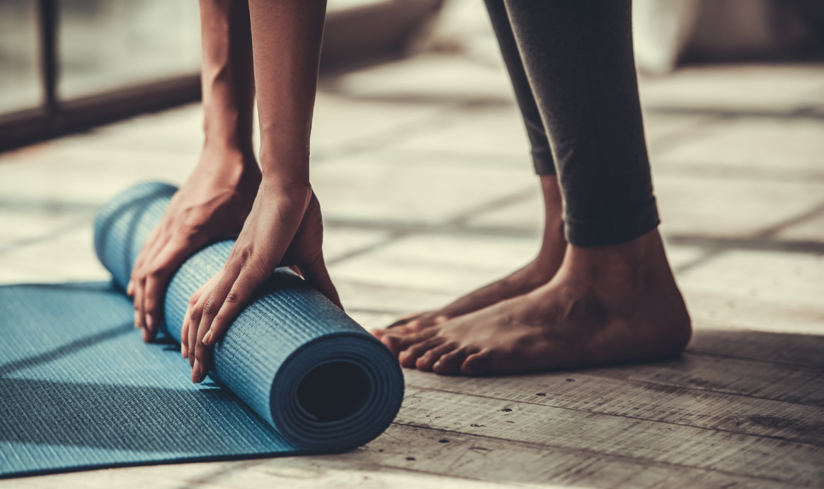 Pilates client rolling up exercise mat