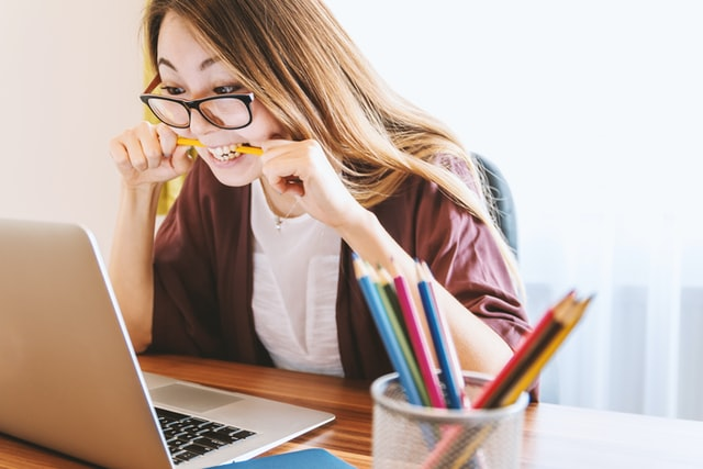 Girl sitting at desk nervously chewing on pen. What causes us to procrastinate?